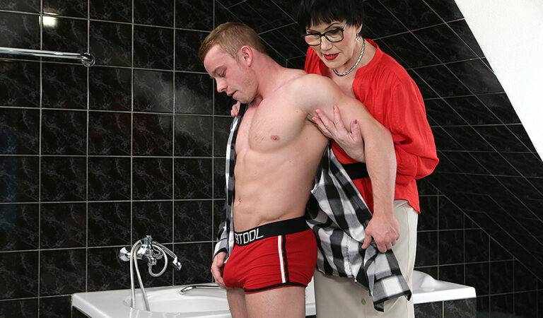 Naughty mature lady catching a toy boy in the bathroom
